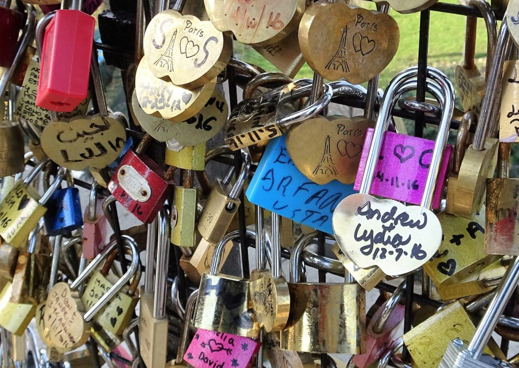 dozens of padlocks with inscriptions, locked to a fence