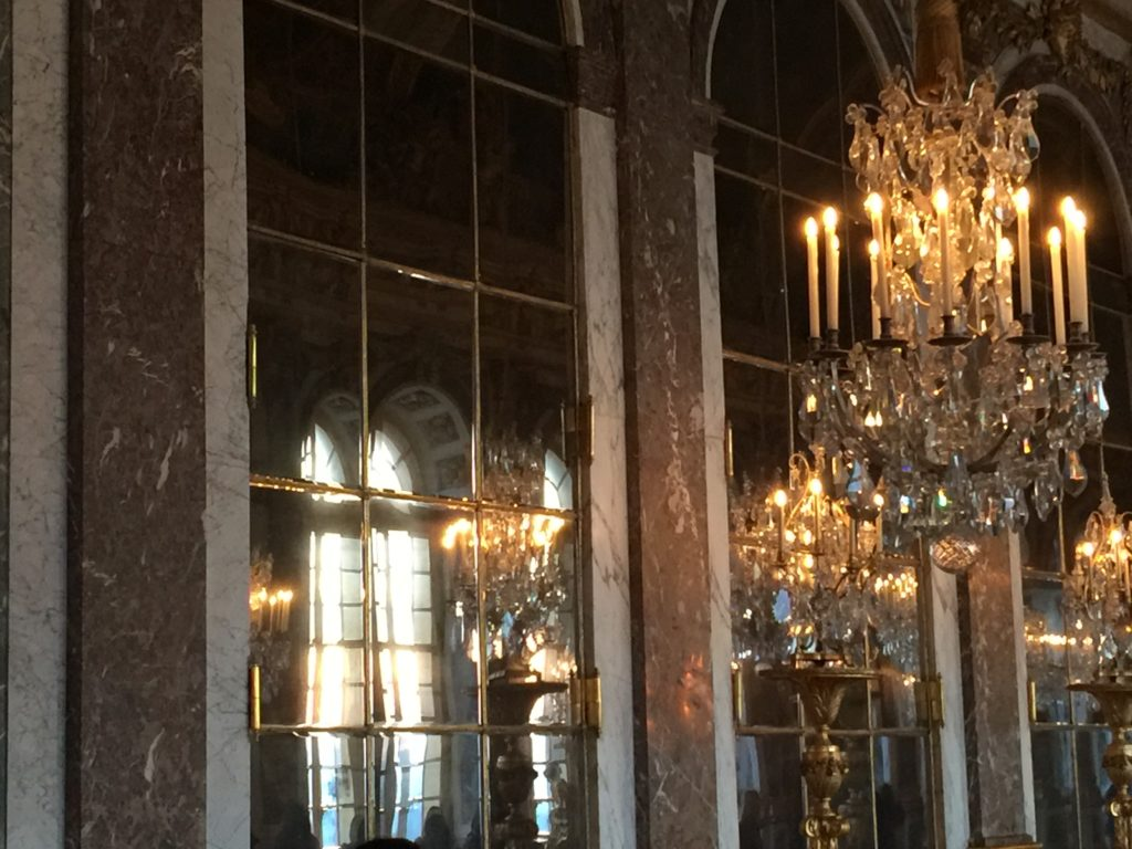 Lit chandelier in the hall with floor to ceiling mirrors