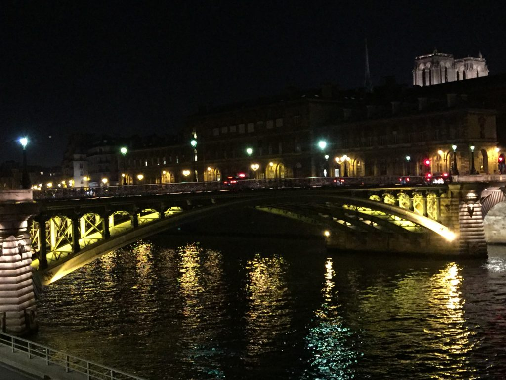 Arched, lit bridge at night over a river